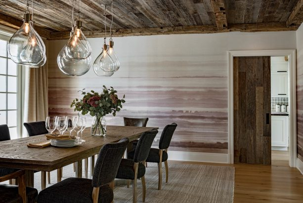 the use of white trim for a wood door in a wood-dominated farmhouse dining room interior