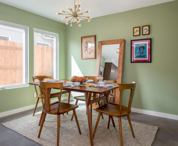 the combination of sage green walls and wooden furniture in a midcentury dining room