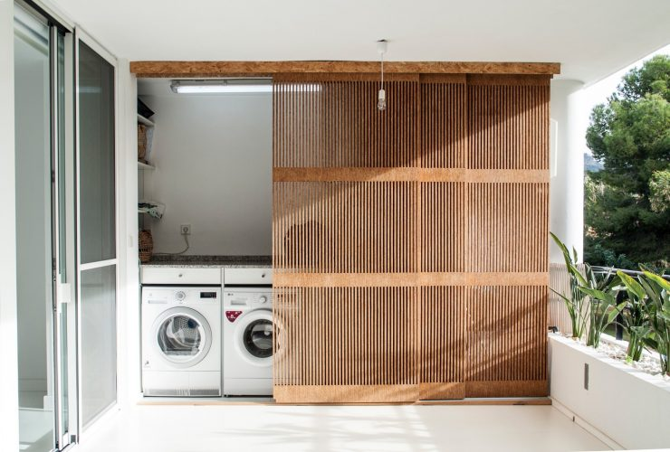 a balcony laundry closet with custom sliding screen doors