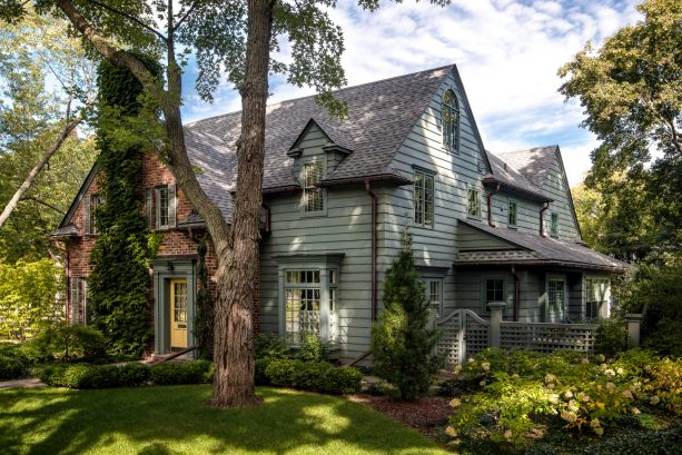 a sage green traditional exterior with grey roof shingles