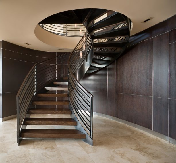 a large and trendy helical open staircase leads to basement