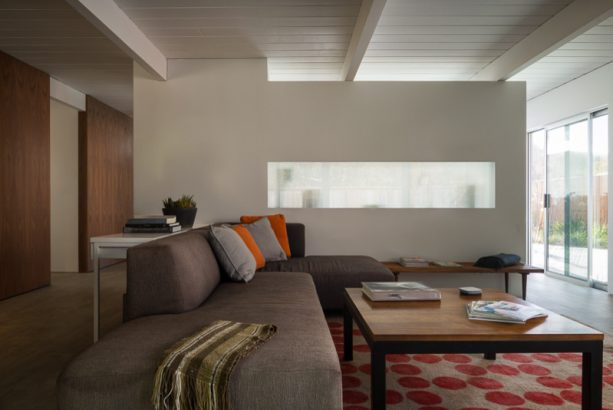 a midcentury living room with long indoor frosted glass window