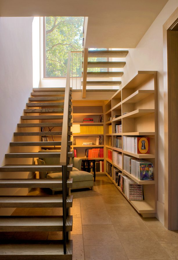 a reading area under an open staircase that leads to a basement