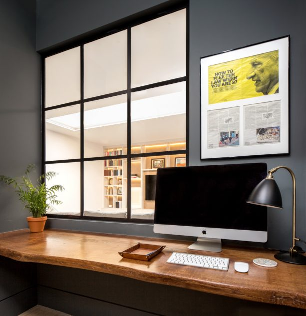 a small home office with glass interior window