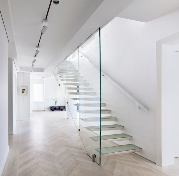 a unique glass open staircase in a contemporary basement design