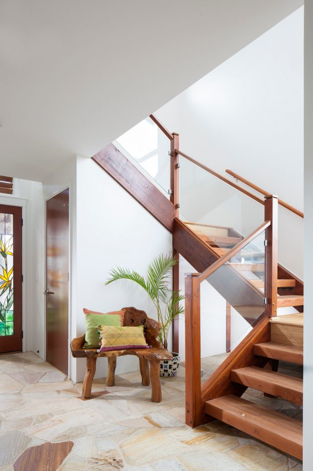 a wood-framed glass railing in a contemporary basement open staircase