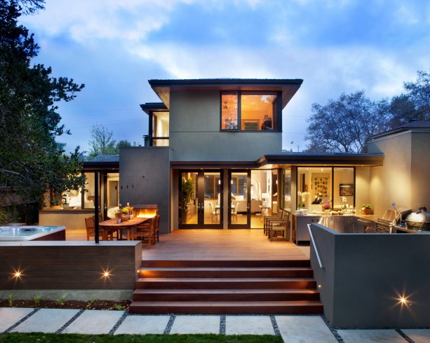 a grey stucco house with brown deck and brown doors and windows