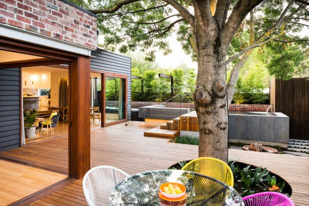 a large decking with clear-stained appearance on the exterior environment of a dark grey house
