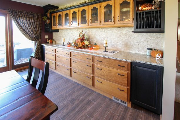 the updated cabinets get black accents, new countertops, and new backsplash
