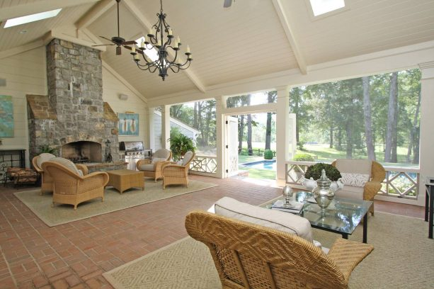a spacious, luxurious traditional screened porch with large stone fireplace