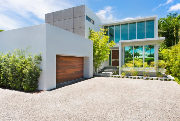 a white boxy garage in front of a beach-front contemporary house