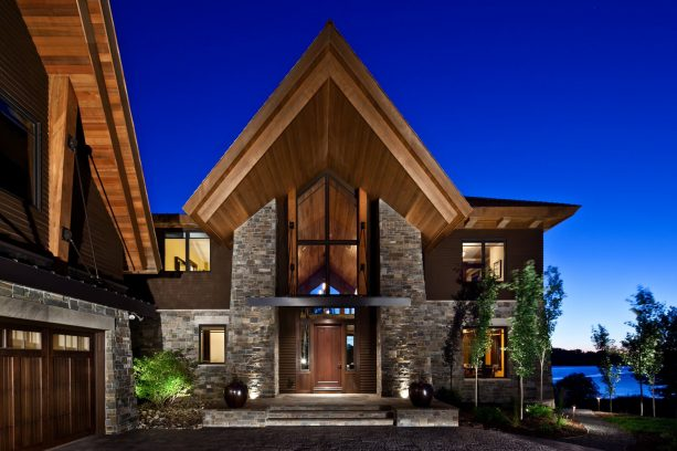 a modern-style mountain house with the mixture of brown-painted siding and stone material