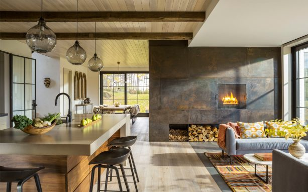 a very stunning metal fireplace in an industrial x farmhouse open-style living interior