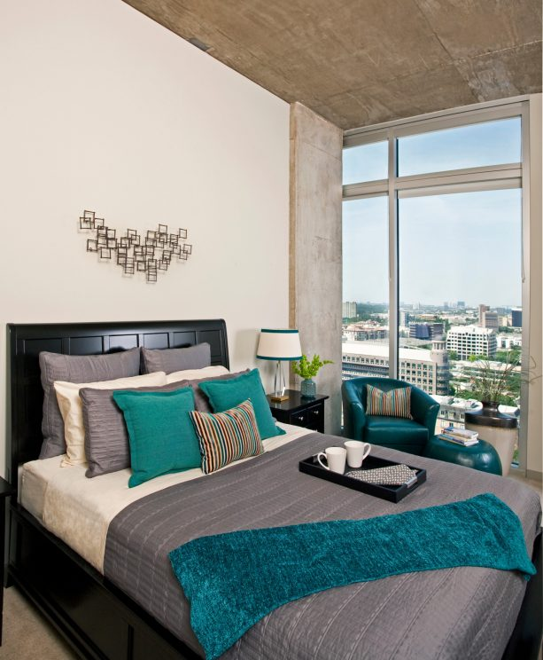 a black bed with grey bedding and teal pillows and throw blanket