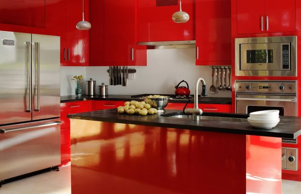 a contemporary kitchen with glossy red cabinets and island, black cabinets, and white backsplash