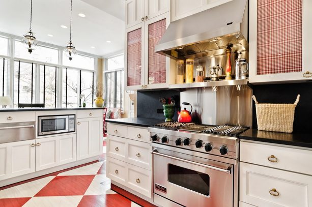 a hardwood flooring is painted in red and white in a traditional black and white kitchen interior