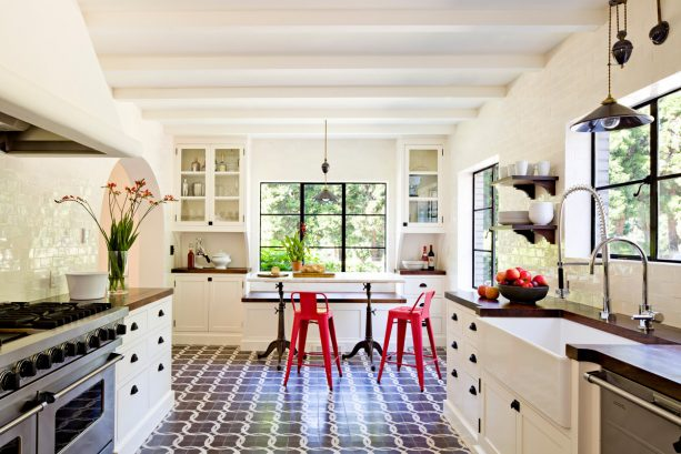 a mediteranean black and white kitchen with breakfast area with red stools