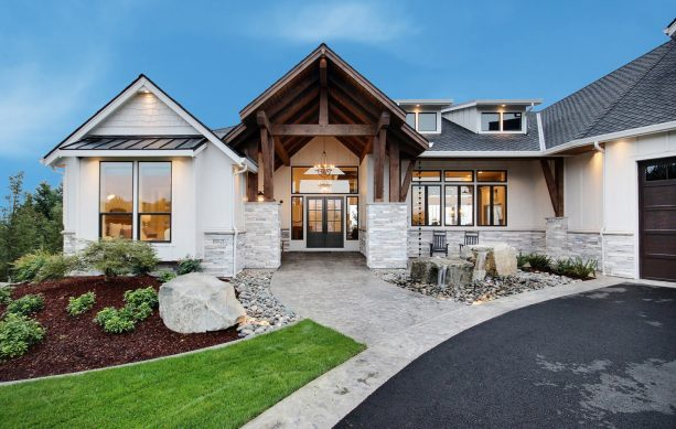 a modern farmhouse exterior with Drift of Mist SE 9166 paint color and stained wood accents
