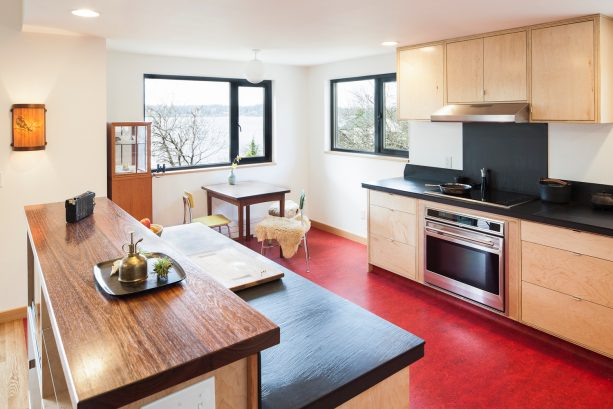 a stunning red flooring in a black and white kitchen completed with wood cabinets