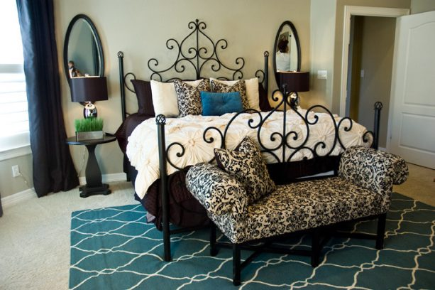 a teal area rug placed under an elegant contemporary metal bed