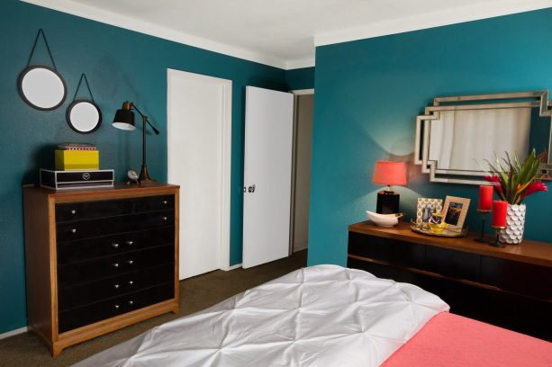 black bedroom furniture with wood accents in front of teal walls