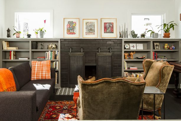 a black-painted brick fireplace with sliding, barn-style screen and a pair of grey bookshelves flanking it