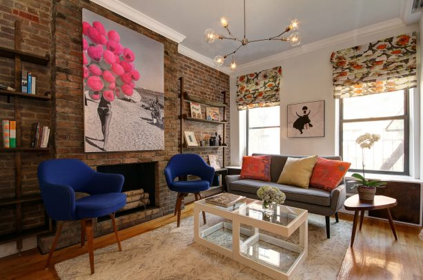 a brick fireplace with custom contemporary wall-mount bookshelves on the sides