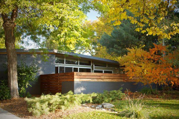 a home exterior showing a striking combination between dark grey cinder block and tigerwood walls