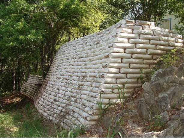 a large retaining wall from concrete bags built behind a house