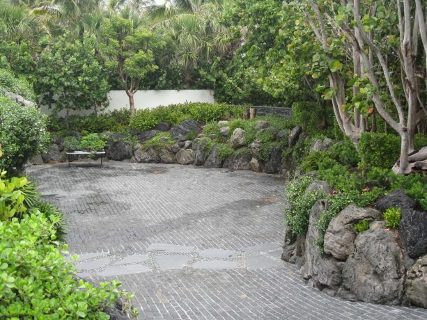 Asian-style driveway landscape with black lava rock retaining wall