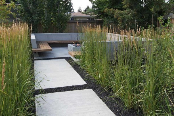 a contemporary landscape with crushed, black lava rocks, concrete pavers, and grassy plants