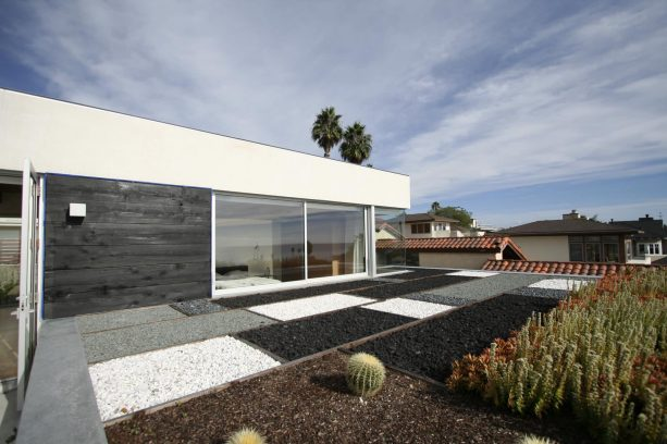 the black lava rock is paired with other rock types to create a modern landscape design