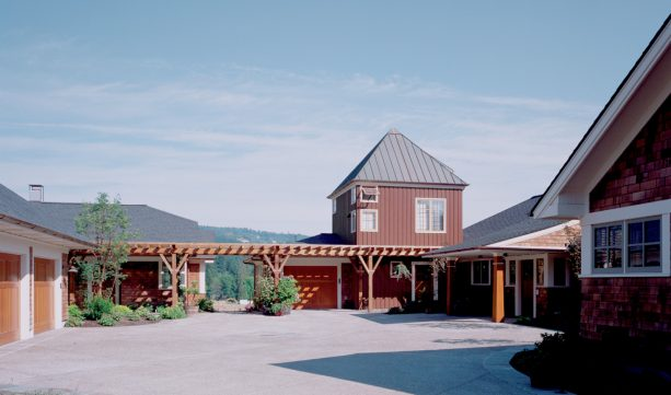 the long walkway between the garage and the house is covered with pergola