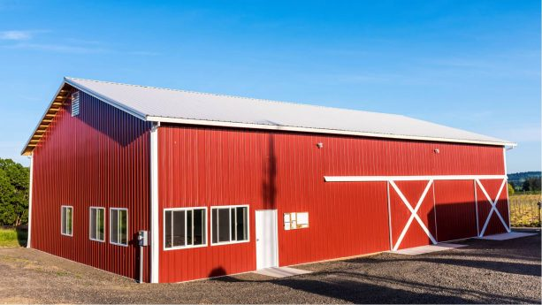 a red pole barn located in agricultural area