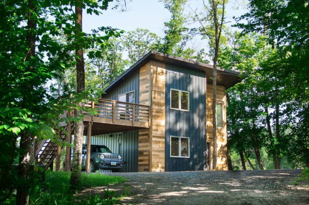 the multicolor tiny house has wooden deck functioned also as a carport cover