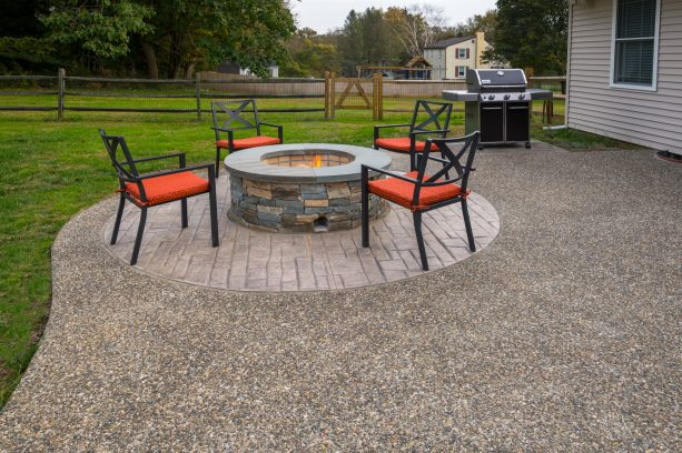 a backyard concrete patio with exposed aggregate and accentuating, round fire pit area