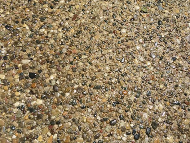 a close-up appearance of an exposed aggregate surface with gloss sealer