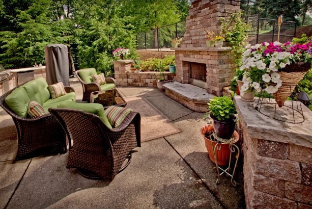 a contemporary patio design looks fabulous with a stone fireplace and exposed aggregate concrete floor