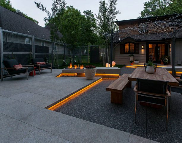 exposed aggregate concrete and stone slabs looks trendy being combined in a contemporary patio design